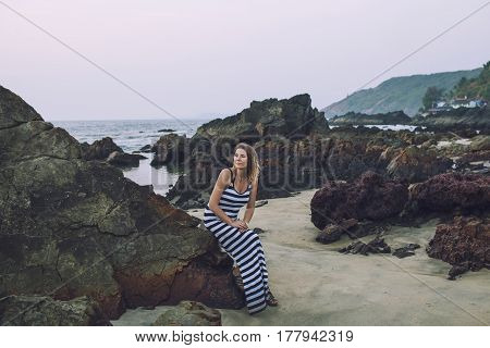 Young Beautiful Happy Woman Sitting On Stones On Sea Shore In Long Dress