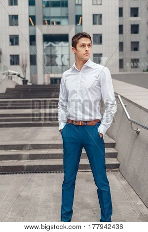 Businessman holds hands in his trouser pockets. Young manager businessman stands near the business center