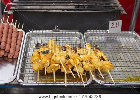 grilled squid pile on cart stall. grilled squid is street food of thailand