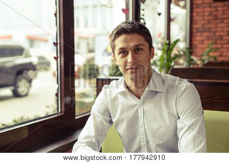 Portrait of a young businesswoman resting between work. Coffee Break in coffee. Young business man looking at camera and posing.