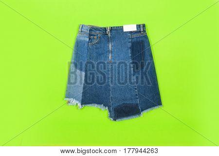 Blue denim skirt isolated on green background