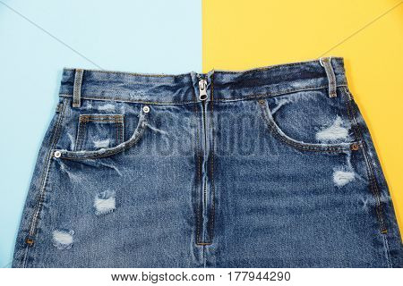 Blue denim skirt isolated on yellow and blue background