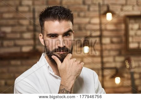 Portrait of bearded man at trendy industrial loft home, looking at camera, thinking.