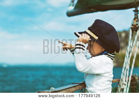 Funny baby captain on board of sailing yacht watching offshore sea on summer cruise. Travel adventure yachting with child on family vacation. Kid clothing in sailor vintage style nautical fashion