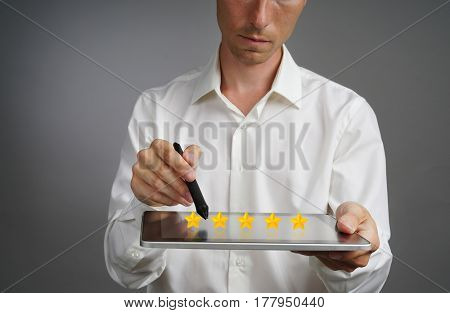 Five star rating or ranking, benchmarking concept. Man with tablet PC assesses service, hotel, restaurant
