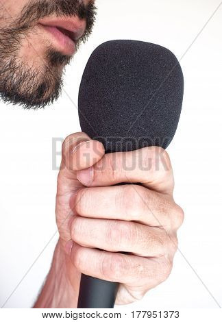 Side view of male mouth with stubble and microphone on white background