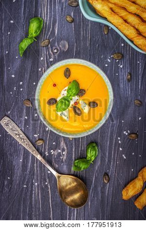 Pumpkin and carrot cream soup with pumpkin seeds and blue cheese on a dark wooden background
