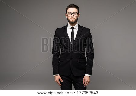 Handsome Young Bearded Businessman In Classic Suit And Looking Away, On A Gray Background
