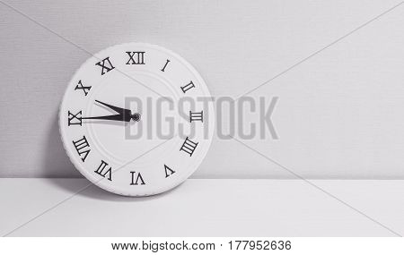 Closeup white clock for decorate show a quarter to ten o'clock or 9:45 a.m. on white wood desk and wallpaper textured background in black and white tone with copy space