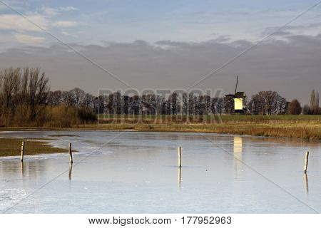 Frozen river foreland from the river Maas near the Dutch village Batenburg with the windmill in the background