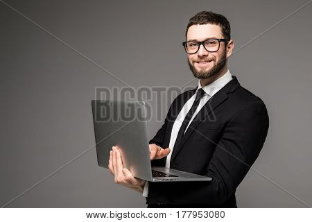Handsome Business Man In Glasses And Suit Holding Laptop In Hands And Writing Something Side View Is