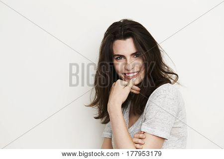 Gorgeous brunette smiling to camera portrait studio