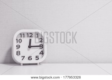 Closeup white clock for decorate show a quarter past twelve o'clock or 12:15 p.m. on white wood desk and cream wallpaper textured background in black and white tone with copy space