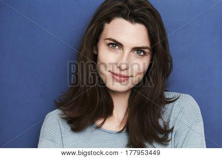 Beautiful green eyed brunette babe in blue studio