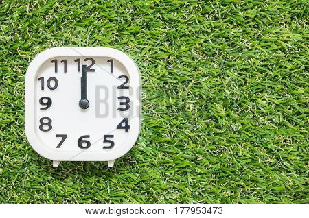 Closeup white clock for decorate in 12 o'clock on green artificial grass floor textured background with copy space