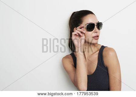 Cool looking Sunglasses babe in studio looking away