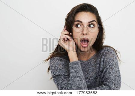 Cute Woman in glasses looking shocked studio