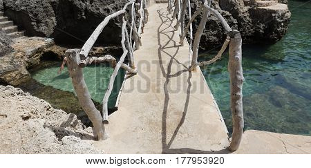 Bridge above the turquoise crystal clear water of Menorca