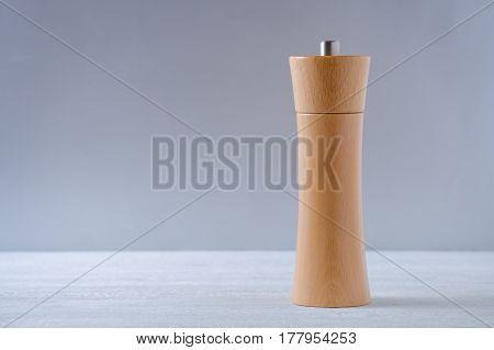 wooden grinder for salt or pepper on gray, horisontal