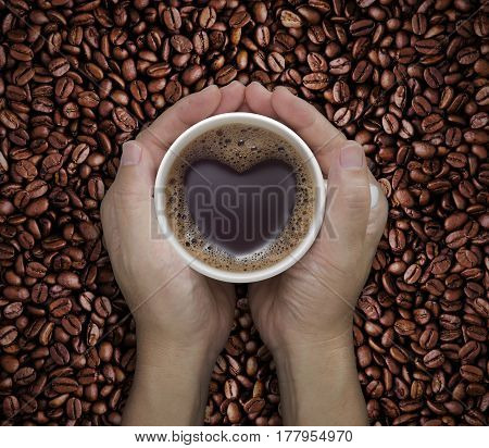 Coffee lover sign - man hands holding cups of coffee with heart shape on coffee beans background. love symbol on fresh coffee mug in male hands - Top view
