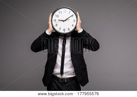 Man In Gray Suit Holding Big Clock Covering His Face