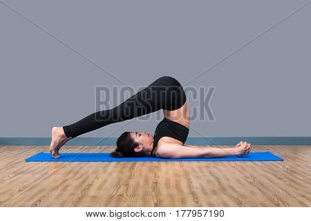Young asian woman enjoy practicing yoga pose at yoga healthy sport gym yoga and meditation have good benefits for health. Photo concept for Yoga Sport and Healthy lifestyle