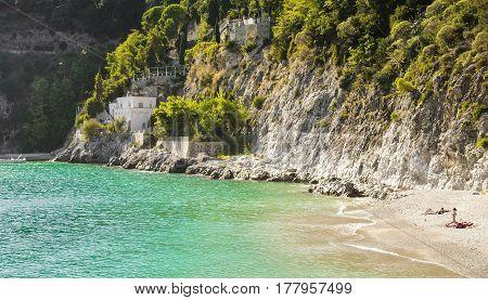 Amalfi Coast, Cetara beach, near Amalfi, Italy. where people are swimming and sunbathing