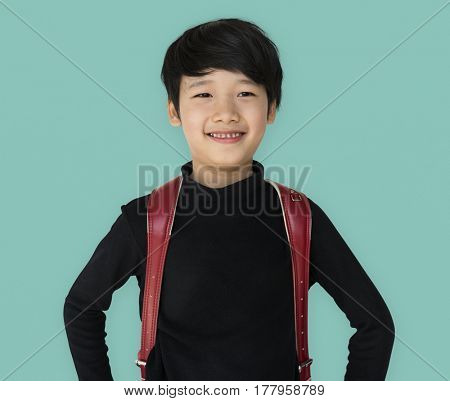Asian ethnicity boy with backpack is smiling