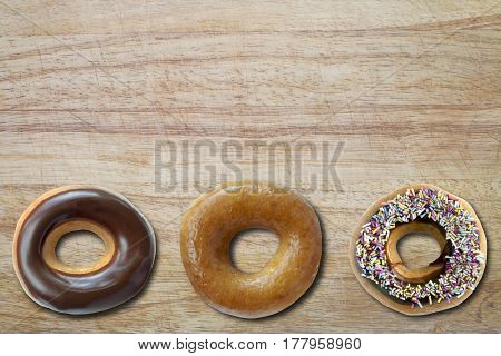 Three coated ring donuts from overhead on a chopping board with copy space