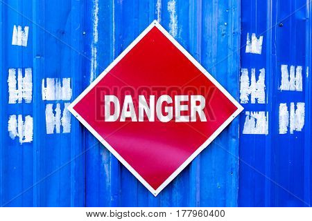 A Red Danger Sign Mounted To A Blue Metal Wall.