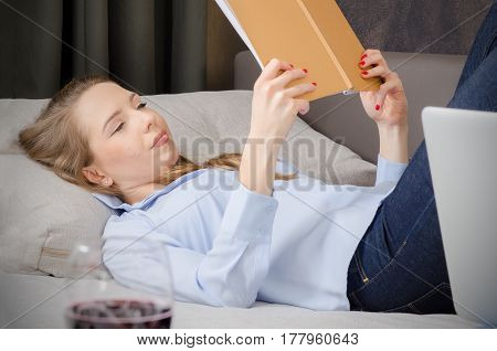 Woman Laying On Sofa And Reading A Book