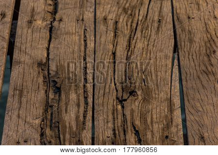 Close up some old wooden blanks of a pier with grains of sand to golden hour lighting.