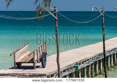 An old wooden luggage trolly waiting to be used at the end of a jetty in a calm tropical sea.