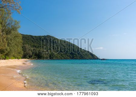 White Sandy Beach Bay With Wooden Pier And Forested Headland In The Distance On A Tropical Island.
