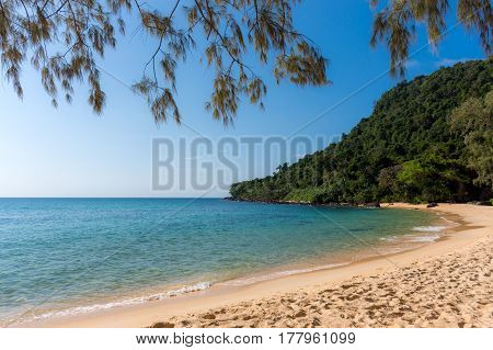 White Sandy Beach Bay With Forested Headland In The Distance On A Tropical Island.