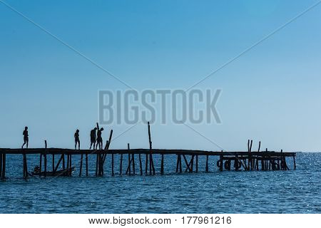 A Silhouetted Group Of Friends Walk Along An Old Wooden Pier