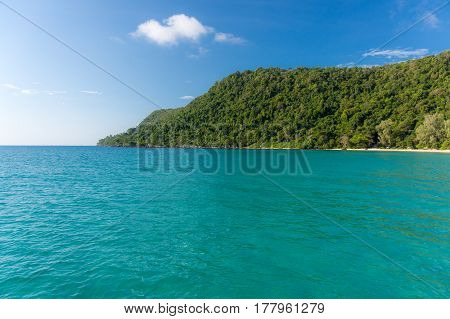 White Sandy Beach Bay With Forested Headland