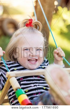 The photo shows a girl swinging on a swing