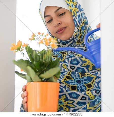 Muslim traditional woman watering flowers at home