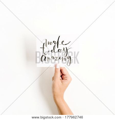 Minimal pale composition with girl's hand holding card with quote Make Today Amazing written in calligraphic style on paper on white background. Flat lay top view