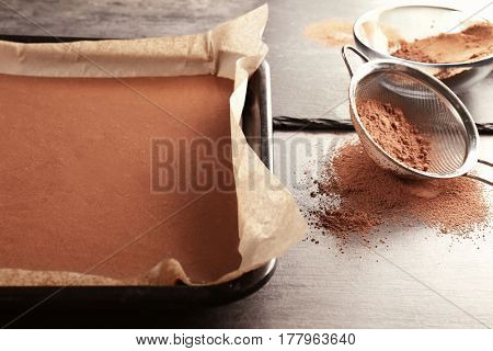 Unbaked cocoa cake in baking tray on table
