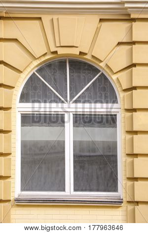Arched white window with sand wall background