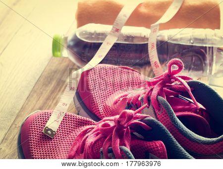 Sneakers towel water and tape measure on wooden floor under sunlight