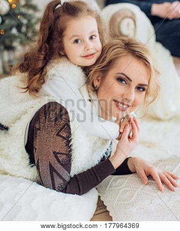 Beautiful young mother and her little daughter near Christmas tree
