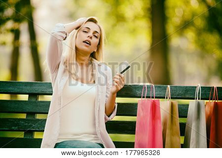 Young woman is sitting in park after shopping. She is nervous because she spent too much money. Intentionally toned.