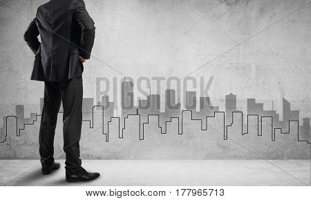 Back view of businessman and sketches of construction project on wall