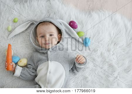 Cute little baby in bunny costume lying on furry rug