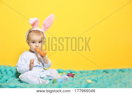 Cute little baby in bunny ears sitting on plaid on color background