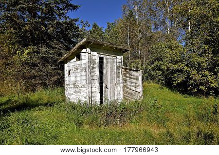 An old white wood peeling outhouse is located along the edge of a woods.