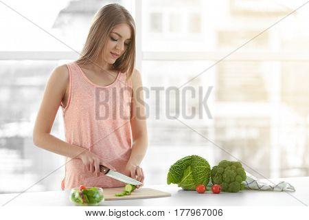 Young beautiful woman making salad at home